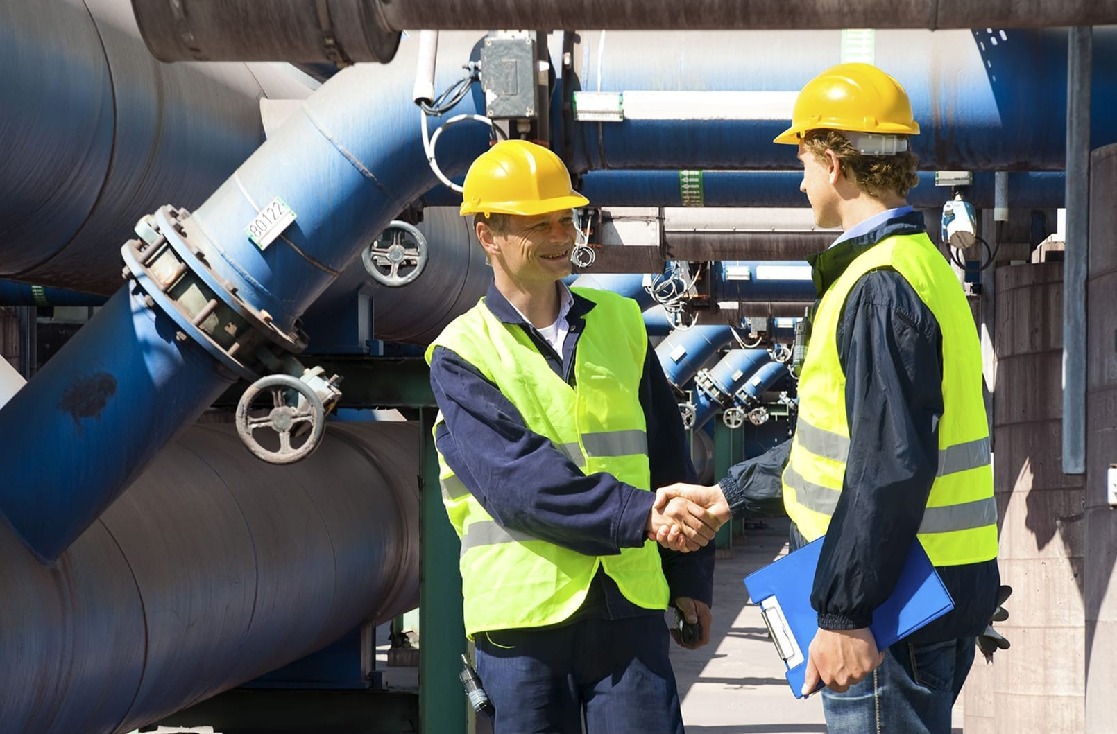 10779441 - two engineers meeting outside at the piping of an industrial waste water cleaning facility